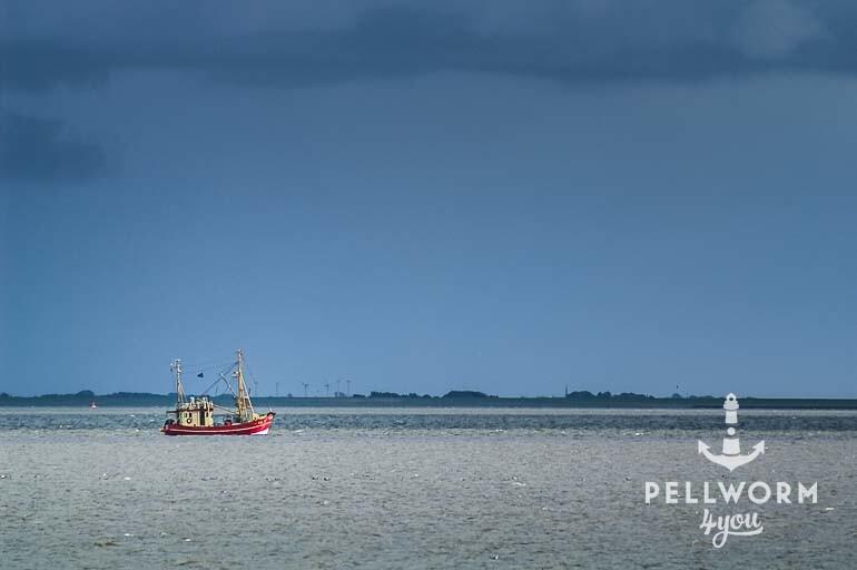 Ein Krabbenkutter fährt an der Insel vorbei