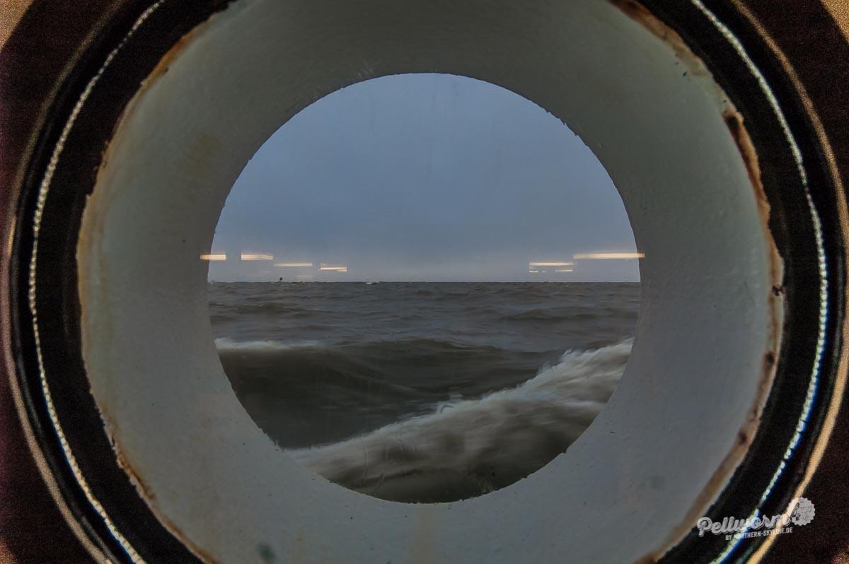 Blick aus dem Bullauge der Fähre Pellworm I auf das Wasser.