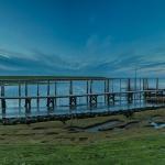 Blau schimmert der Himmel über dem Yachthafen und der Hafeneinfahrt auf Pellworm