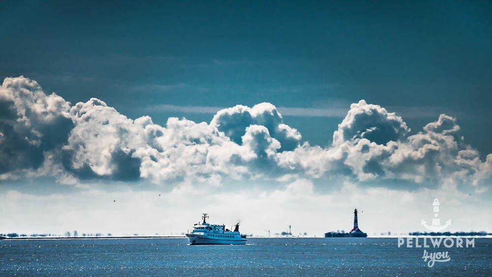 Das Ausflugsschiff Adler V fährt an der Insel Pellworm vorbei. Im Hintergrund ist der Westerhever Leuchtturm zu erkennen.