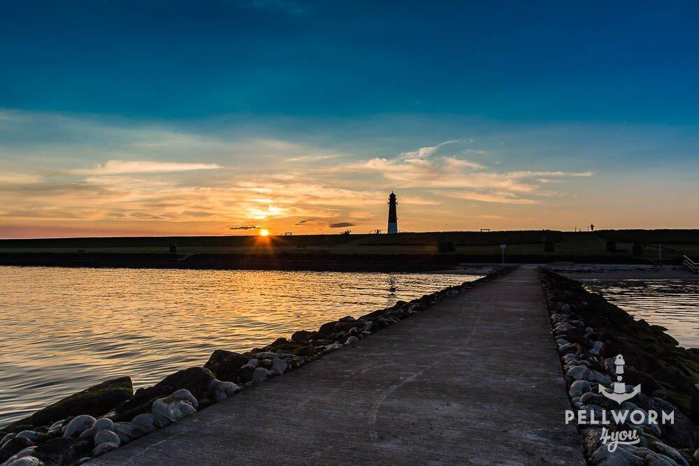 Die Badebuhne im Vordergrund mit dem Pellwormer Leuchtturm im Sonnenuntergang
