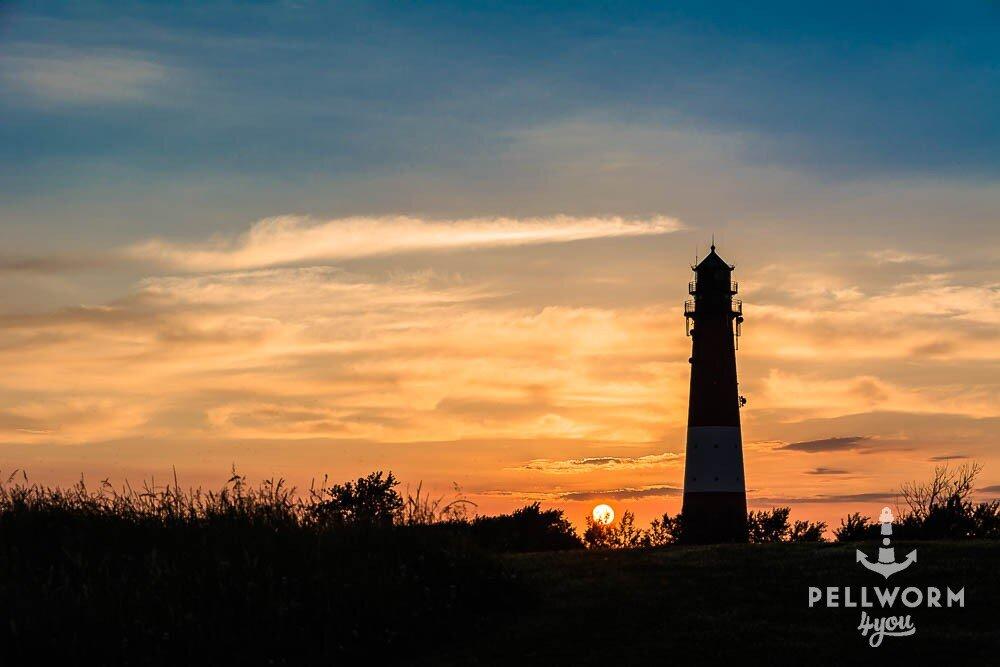 Pellworms Leuchtturm steht im Licht der rot-orange untergehenden Abendsonne - das ist Urlaub pur