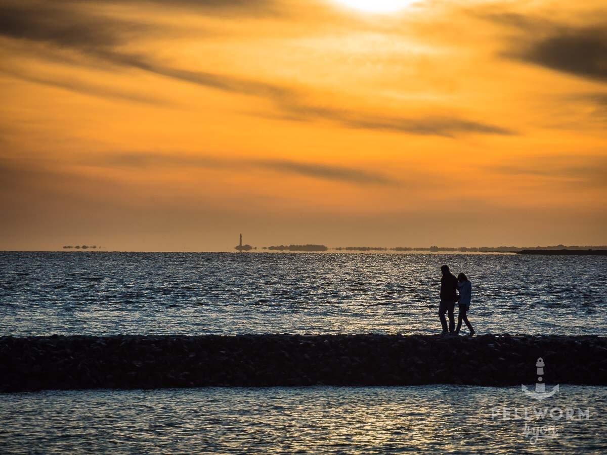 Zwei Urlauber spazieren am Anleger Hooger Fähre auf Pellworm im Sonnenuntergang