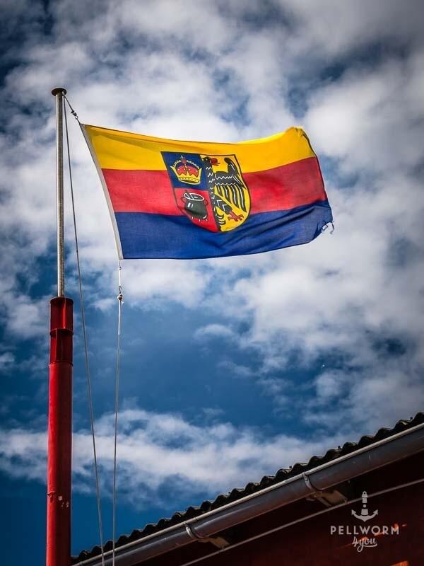 Die Flagge Nordfrieslands weht am Schifffahrtsmuseum im Hafen von Pellworm