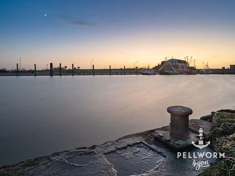 Hafenkante mit Poller und im Hintergrund der Hafen von Tammensiel auf der Insel Pellworm